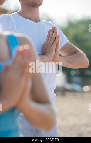 Fitness, sport, amitié et vie concept - smiling couple faire des exercices de yoga méditation sur la plage au matin Banque D'Images