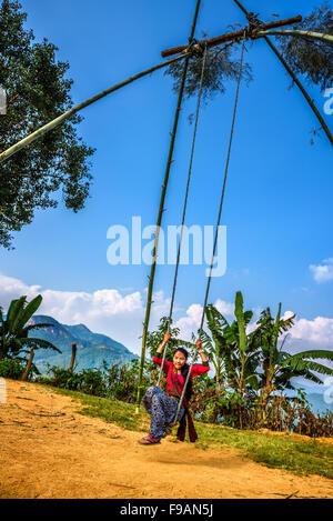 Jeune fille népalaise jouant sur une balançoire bambou traditionnel appelé linge ping. Banque D'Images
