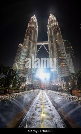 Fontaine en face des tours Petronas illuminé la nuit, Kuala Lumpur, Malaisie Banque D'Images