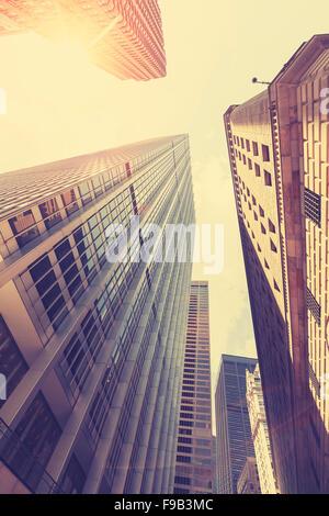 Retro photo stylisée des gratte-ciel de Manhattan au coucher du soleil avec l'effet lens flare, New York City, USA. Banque D'Images