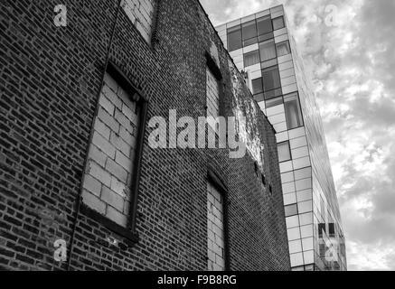 Un contraste d'un vieux bâtiment en brique avec une tour moderne en verre en monochrome. Tourné à New York. Banque D'Images