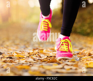 Close up de pieds d'un coureur s'exécutant dans les feuilles d'automne d'entraînement Banque D'Images