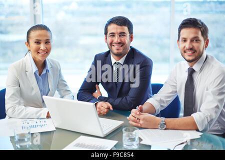 Portrait d'une équipe positive assis à une table Banque D'Images