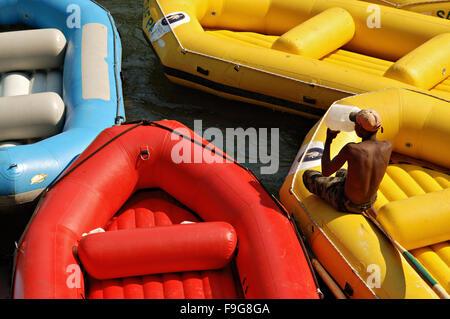 Homme africain assis et boire sur un radeau jaune sur le fleuve Zambèze en Zambie Banque D'Images