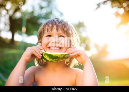Cute little girl eating watermelon en extérieur dans le jardin d'été Banque D'Images