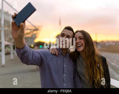 Jeune couple de prendre un smartphone avec selfies au crépuscule du soir Banque D'Images