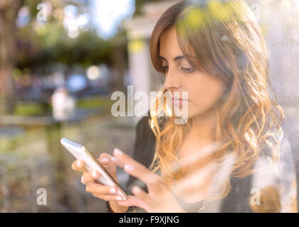 Pensive young woman looking at her smartphone Banque D'Images
