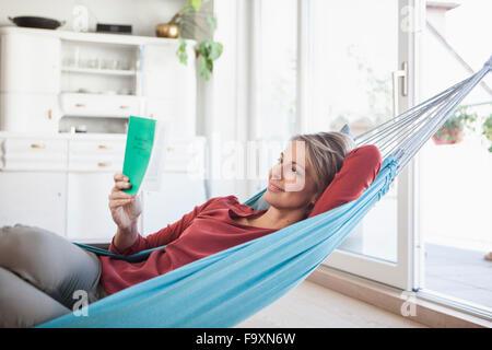 Smiling woman at home couché dans un hamac reading book Banque D'Images