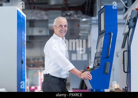 Portrait of smiling man at contrôle dans un hall industriel Banque D'Images
