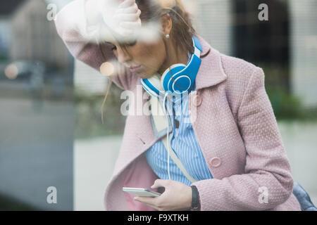 Young woman leaning à façade de verre à on cell phone Banque D'Images