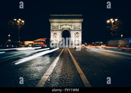 Le trafic sur l'Avenue des Champs-Élysées et l'Arc de Triomphe de nuit à Paris, France. Banque D'Images