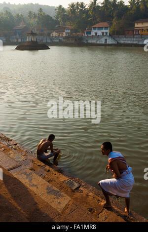 Deux hommes se baigner de façon rituelle hindoue dans la ville sainte du réservoir ou koti teertha tank le matin Banque D'Images