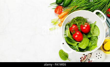 Jardin de légumes biologiques frais dans une passoire bol blanc sur fond de pierre rustique, concept de cuisine Banque D'Images