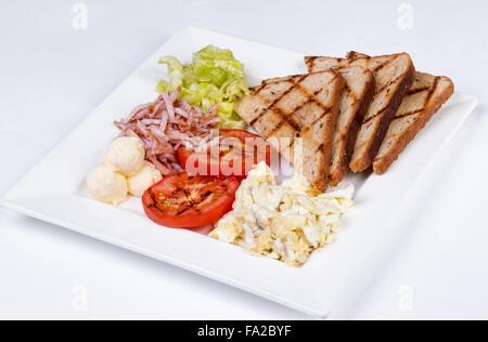 Petit-déjeuner anglais traditionnel avec des œufs brouillés, tomates, pommes de terre, pain grillé et salade fraîche Banque D'Images