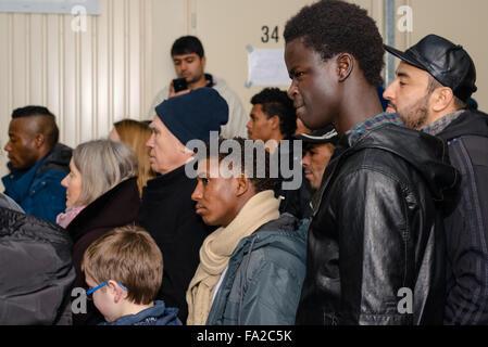 Scharnhausen, Allemagne - le 20 décembre 2015: les réfugiés de la Libye, le Nigeria, l'Afghanistan, le Pakistan, l'Erythrée, la Gambie, le Togo, l'Algérie, la Tunisie et d'autres pays sont à l'écoute de l'histoire de Noël Chrétien pendant une fête de Noël organisée par les volontaires dans le camp de réfugiés de Scharnhausen près de Stuttgart en Allemagne avec voisins allemands et d'autres bénévoles. Des milliers de réfugiés sont en ce moment à fuir vers l'Allemagne, une demande d'asile étant donné qu'ils sont menacés par l'ISIS et guerres civiles dans leurs pays d'origine.