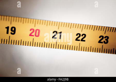 Règle métallique ruban à mesurer montrant measuement en centimètres (cm) numéros sur fond uni Banque D'Images