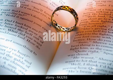 Situé sur l'anneau d'un livre ouvert avec l'ombre en forme de cœur Banque D'Images