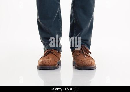 Closeup portrait of a human jambes en jeans et bottes isolé sur fond blanc Banque D'Images