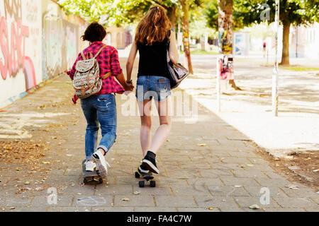 Vue arrière du girls holding hands et la planche à roulettes sur sentier Banque D'Images