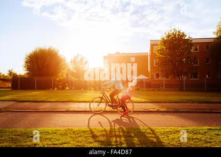 Vue latérale des femmes sportive équitation location sur street pendant le coucher du soleil Banque D'Images
