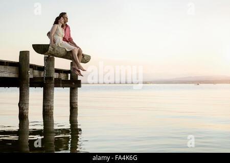 Young couple sitting on pier surplombant le lac, Bavière, Allemagne