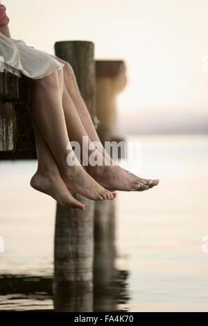 Couple les jambes pendantes sur la jetée, Bavière, Allemagne Banque D'Images