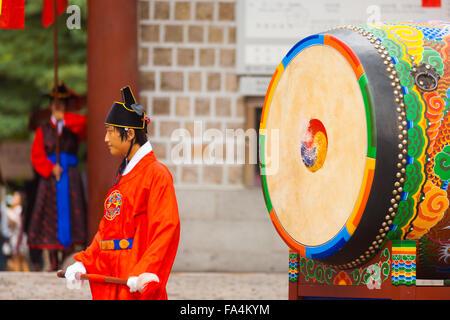 Grand batteur traditionnel coréen en rouge costume en attente de bang un ancien palais Deoksugung à tambour Banque D'Images