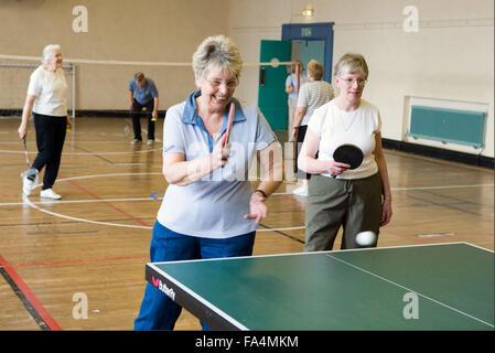 Groupe de femmes âgées à jouer au tennis de table et de badminton en salle de sport, Banque D'Images