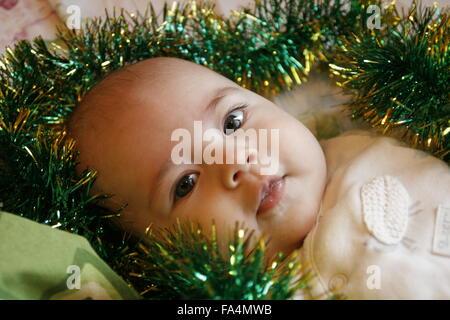 Un petit bébé couché dans un lit avec une guirlande de noël