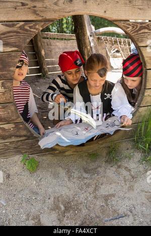 Les filles habillés en pirates regardant une carte au trésor dans l'aire d'aventure, Bavière, Allemagne Banque D'Images