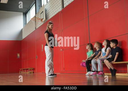Pour l'enseignant de donner des conseils aux enfants dans les jeux de groupe sports hall, Munich, Bavière, Allemagne Banque D'Images