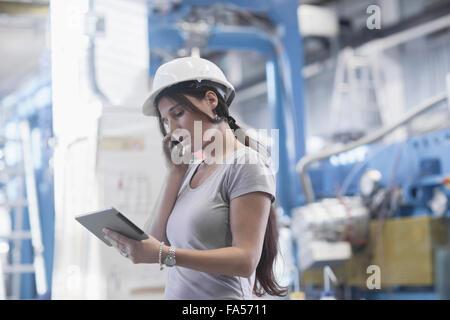 Ingénieur femelle à l'aide d'une tablette numérique et le téléphone mobile dans une installation industrielle, Bade-Wurtemberg, Allemagne