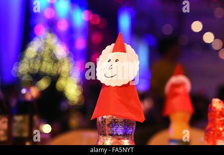 Berlin, Allemagne. Dec 21, 2015. Santa Claus chiffres ont été placés au-dessus des bouteilles de décoration traditionnelle Banque D'Images
