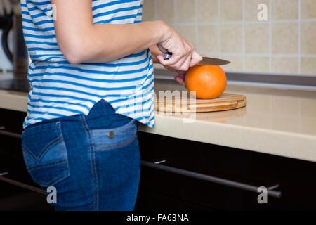 Jeune femme slim en jeans et t-shirt à rayures de pamplemousse coupe dans la cuisine à la maison Banque D'Images
