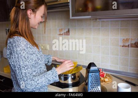 Jolie rousse souriante jeune femme en gris chandail tricoté faire des pâtes dans la cuisine Banque D'Images