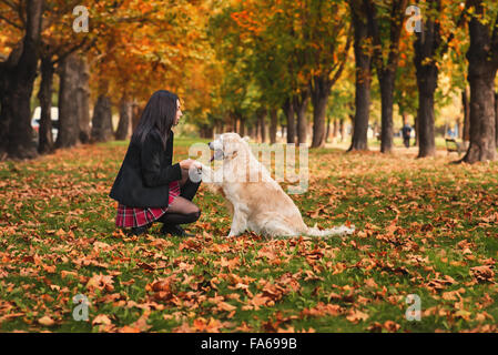 Girl sitting in park with her dog Banque D'Images