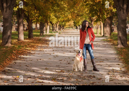 Woman standing in park with her dog Banque D'Images