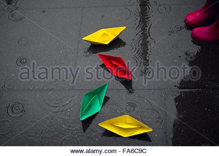 Les bateaux de papier de couleur sur le sol sous la pluie Banque D'Images