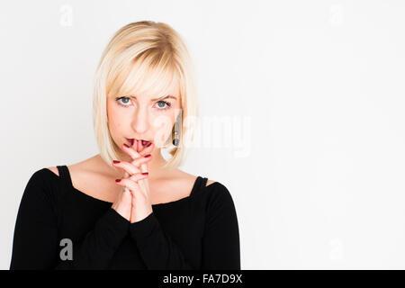 Choix de vie et la prise de décision: Une jeune femme brune mince blonde blonde girl, penser, réfléchir, réfléchie, inquiets à cause de doute incertain indécis UK