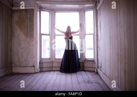 Une jeune femme aux cheveux blonds mince portant une longue robe de bal robe seul dans une chambre à l'abandon de Banque D'Images