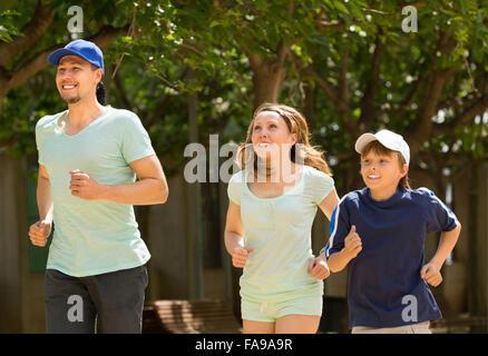 Les parents heureux avec leur fils adolescent du jogging dans le parc Banque D'Images