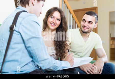 Couple positif commenter les détails de l'assurance privée avec agent Banque D'Images