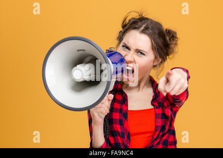 Agacé furieux jeune femme en chemise à carreaux et haut-parleur criant en pointant sur vous sur fond jaune