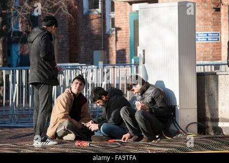 Réfugiés du Pakistan parlent entre eux en sur le terrain de l'Office d'état de la Santé et des affaires sociales (LaGeSo) à Berlin, Allemagne, 24 décembre 2015. Au cours des trois jours de Noël que le squelette est l'équipe du personnel travaillant à l'LaGeSo. Photo: PAUL ZINKEN/dpa