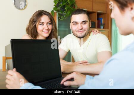 Heureux couple positive commenter les détails de l'assurance privée avec agent Banque D'Images