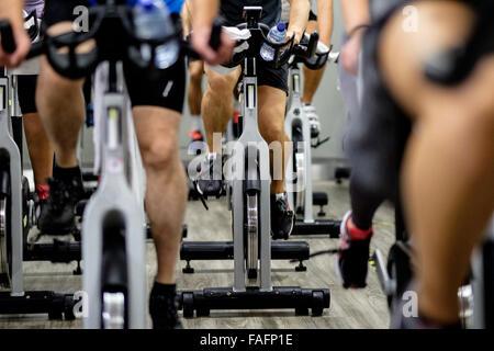 Les bicyclettes stationnaires pendant un cours de gym spinning Banque D'Images