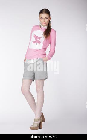 Jeune modèle expressif dans un style décontracté sur fond gris. Banque D'Images