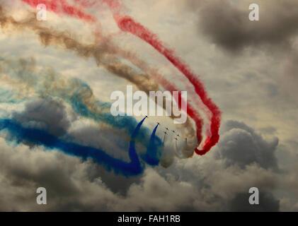 Des flèches rouges RAF Aerobatic Display Team peindre un ciel d'orage avec rouge blanc et bleu fumée. Banque D'Images