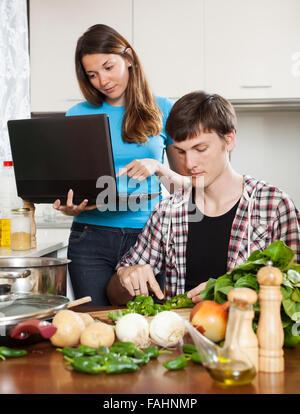 L'homme à la cuisson des aliments alors que woman looking at laptop in home cuisine Banque D'Images