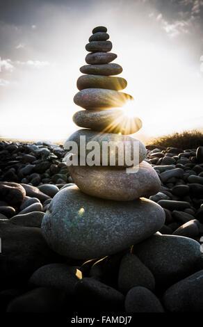 La lumière du soleil du matin brille à travers une pile de galets sur une plage. Banque D'Images